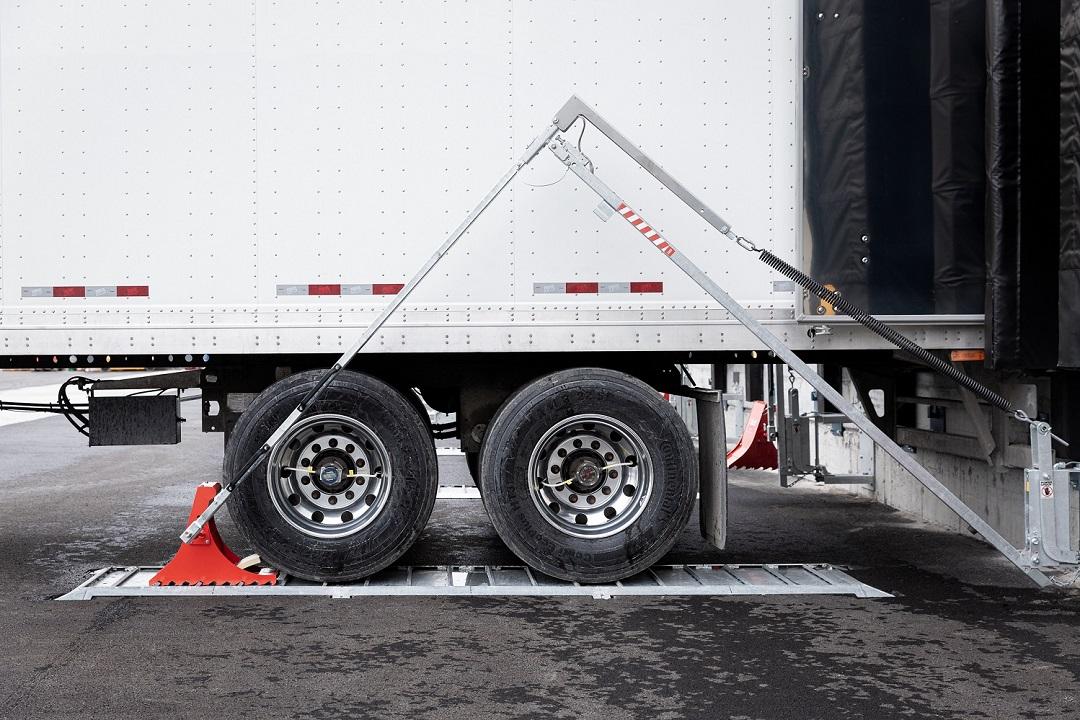 Bloque-roue POWERCHOCK 5 mis en place devant roue camion sur plaque au sol