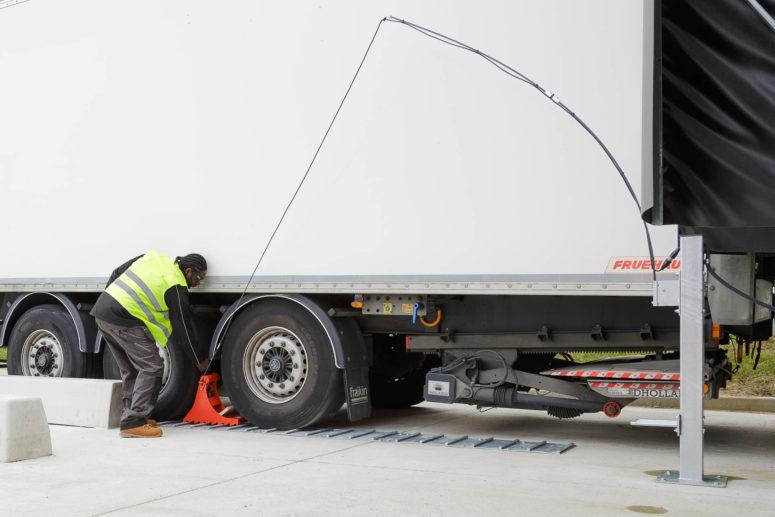 Mise en place du POWERCHOCK 3 par chauffeur camion devant roue