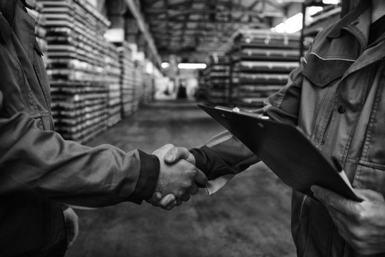 Poignée de main dans entrepôt logistique