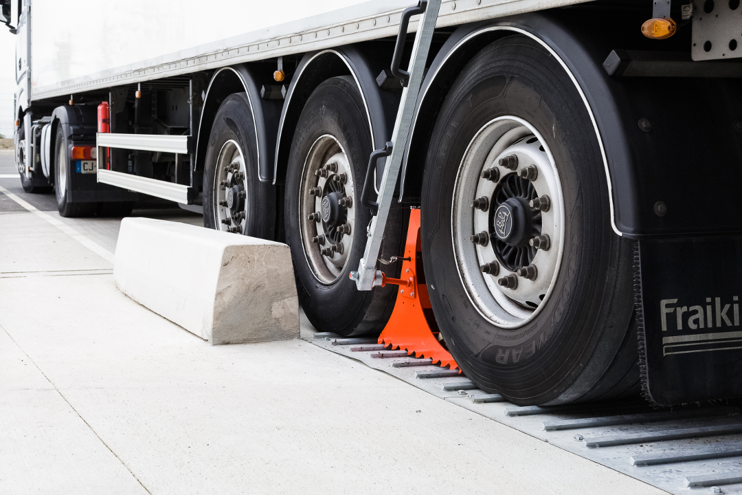 Wheel chock POWERCHOCK 5 set up in front of truck wheel on ground plate