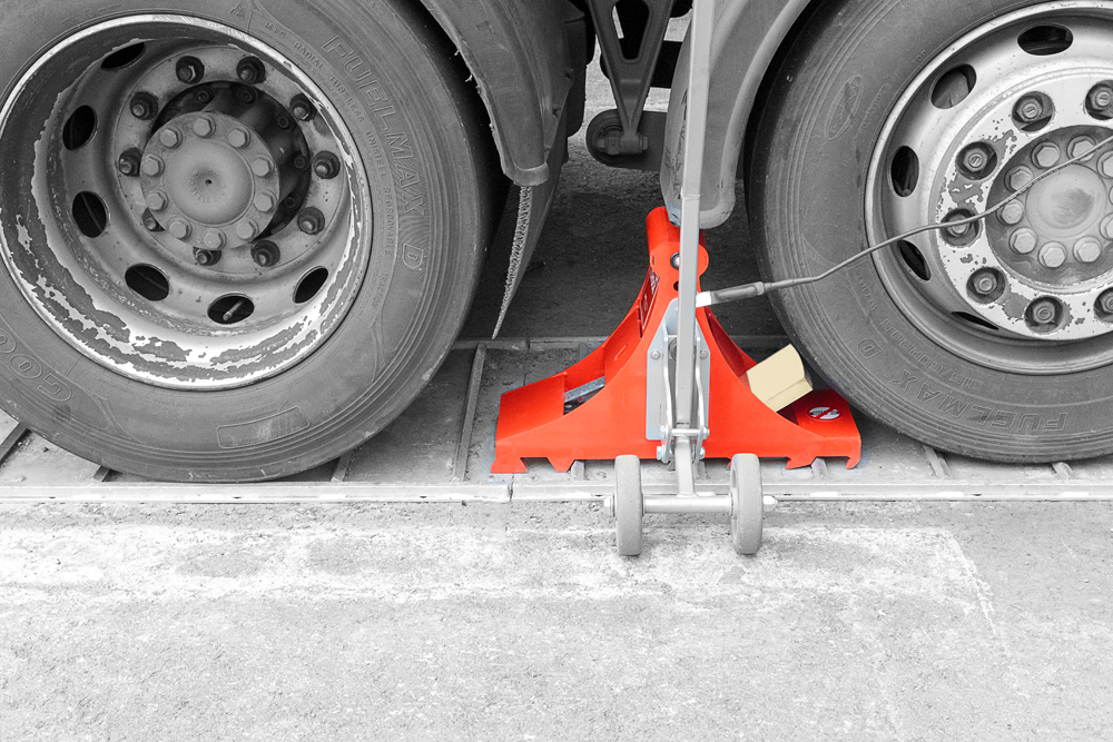 Wheel chock POWERCHOCK 9 set up in front of truck wheel on ground plate